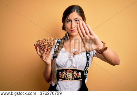 Young brunette german woman wearing traditional Octoberfest dress holding bowl with pretzels with open hand doing stop sign with serious and confident expression, defense gesture
