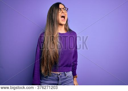 Young beautiful smart woman wearing glasses over purple isolated background angry and mad screaming frustrated and furious, shouting with anger. Rage and aggressive concept.