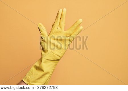 Hand of caucasian young man with cleaning glove over isolated yellow background greeting doing Vulcan salute, showing hand palm and fingers, freak culture