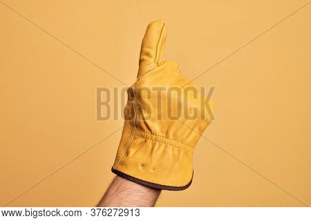 Hand of caucasian young man with gardener glove over isolated yellow background counting number one using index finger, showing idea and understanding