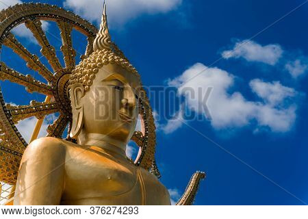 Golden Buddha Statue In A Buddhist Temple In Thailand Against The Blue Sky. Buddha And The Wheel Of