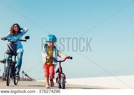 Little Kid Riding A Balance Bike With His Mother On A Bicycle