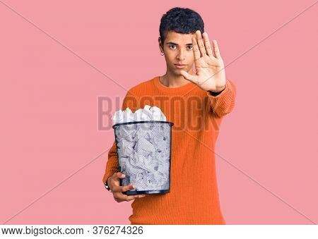 Young african amercian man holding paper bin full of crumpled papers with open hand doing stop sign with serious and confident expression, defense gesture