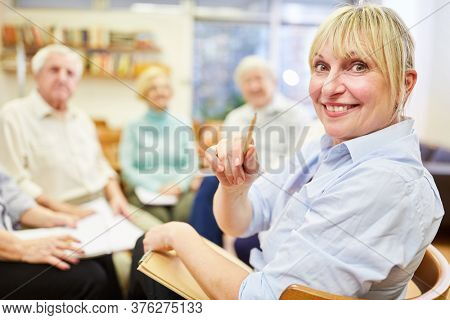Smiling woman as a psychotherapist or a doctor with a group of seniors