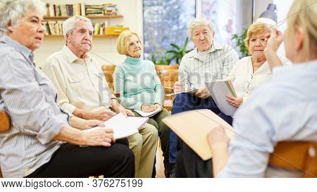 Psychotherapist in group therapy with senior citizens in a retirement home