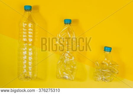 Horizontal Color Image With An Overhead View Of A Transparent And Crushed Plastic Bottles With Blue