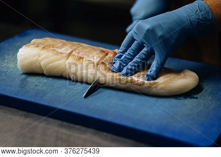 Close-up On Hands In Blue Latex Gloves Cutting Raw Fish On Chopping Board