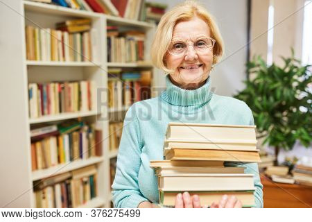 Happy senior woman as a librarian or antiquarian with a stack of books
