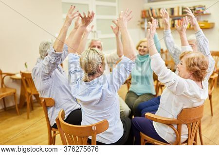 Group of seniors in old people's home doing sitting exercises or exercise therapy exercise