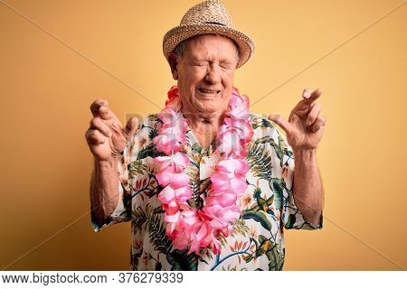 Grey haired senior man wearing summer hat and hawaiian lei over yellow background gesturing finger crossed smiling with hope and eyes closed. Luck and superstitious concept.
