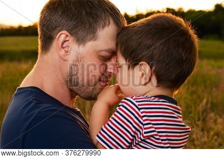 Dad Holds His Young Son In His Arms And Hugs Him In A Summer Field At Sunset In The Evening. Dads Lo