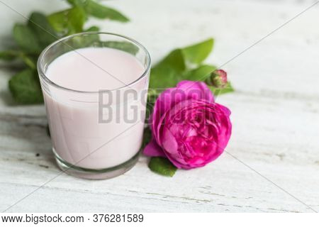 Ayurvedic Drink Pink Milk Or Matcha. A Glass Of Refreshing Cocktail Stands On A Wooden White Backgro