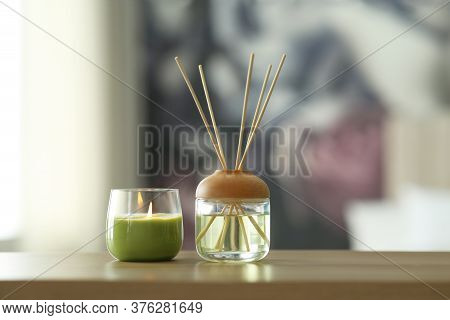 Aromatic Reed Air Freshener And Scented Candle On Table Indoors