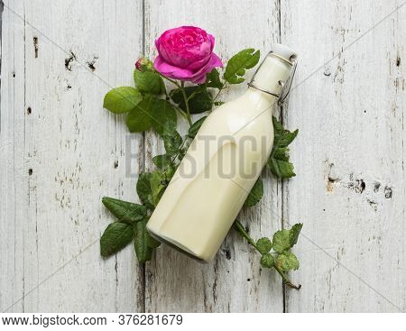 Ayurvedic Drink Pink Milk Or Matcha. A Glass Bottle Of Milk Lies On A Table With A Pink Rose. Top Vi