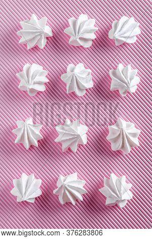 Flat Lay With Delicate White Meringue Cookies. Twelve Meringues Are Lying In Rows On Pink Striped Te