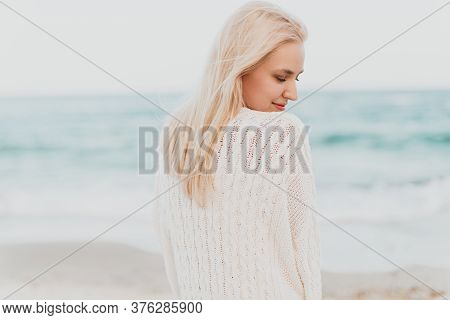 Back View Of Sensual Relaxed Young Blond Female In Stylish White Knitwear Smiling While Enjoying Fre
