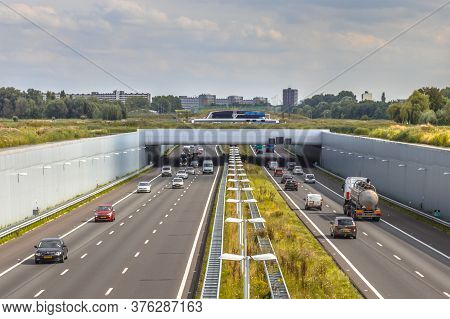 Afternoon Traffic On A4 Motorway Near The Hague Randstad Area. Highway Crossing Aquaduct Tunnel With
