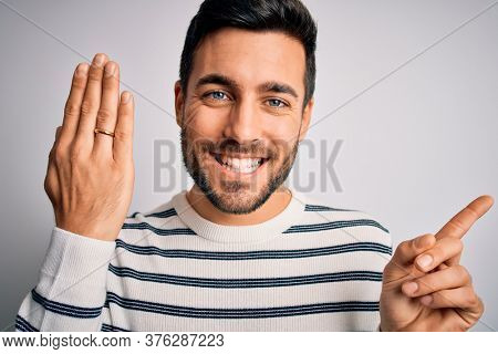 Handsome man with beard showing alliance ring marriage on finger over white background very happy pointing with hand and finger to the side