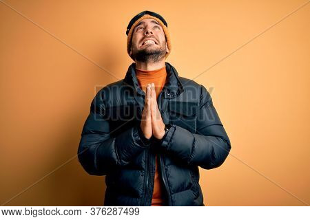 Young handsome skier man with beard wearing snow sportswear and ski goggles begging and praying with hands together with hope expression on face very emotional and worried. Begging.