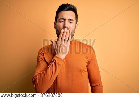 Young handsome man with beard wearing casual sweater standing over yellow background bored yawning tired covering mouth with hand. Restless and sleepiness.