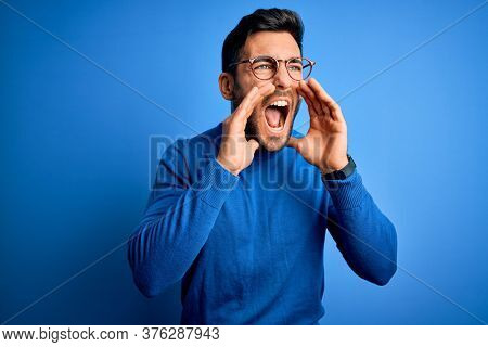 Young handsome man with beard wearing casual sweater and glasses over blue background Shouting angry out loud with hands over mouth