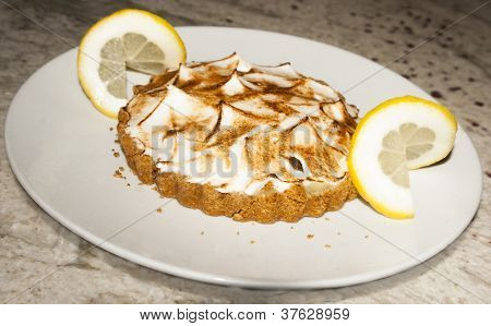 Lemon meringue tart on white plate with lemon slices