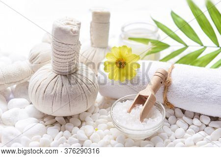Spa setting with Green palm, bottles of essential oil with , herbal ball, salt in bowl ,candle , herbal ,ball ,spoon on pile of white stones ,yellow flower,,green palm