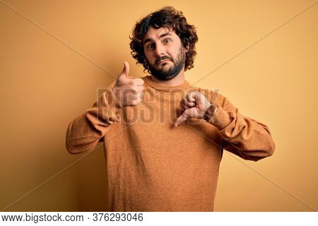 Young handsome man with beard wearing casual sweater standing over yellow background Doing thumbs up and down, disagreement and agreement expression. Crazy conflict