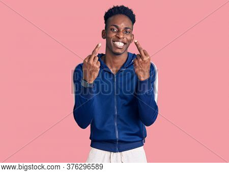 Young african american man wearing sportswear showing middle finger doing fuck you bad expression, provocation and rude attitude. screaming excited