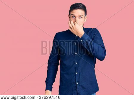 Young handsome man wearing casual shirt smelling something stinky and disgusting, intolerable smell, holding breath with fingers on nose. bad smell