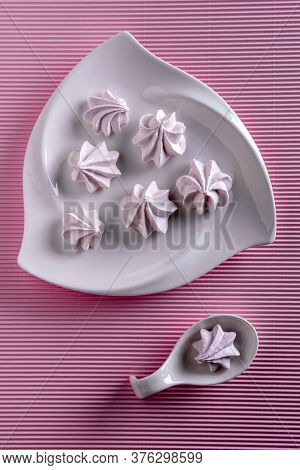 Flat Lay With Delicate Pink Meringue Cookies. Few Meringues Are On White Porcelain Plate And One Is