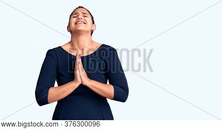 Young beautiful brunette woman wearing casual dress begging and praying with hands together with hope expression on face very emotional and worried. begging.