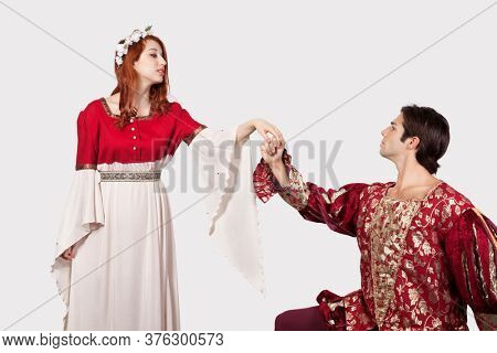 Young man in old-fashioned costumes holding princess's hand against gray background