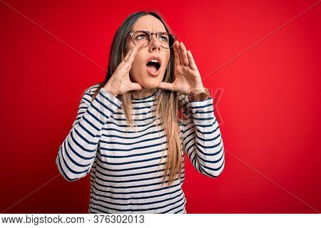 Young beautiful blonde woman with blue eyes wearing glasses standing over red background Shouting angry out loud with hands over mouth