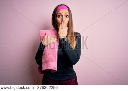 Young fitness woman wearing sport workout clothes using towel over pink background cover mouth with hand shocked with shame for mistake, expression of fear, scared in silence, secret concept