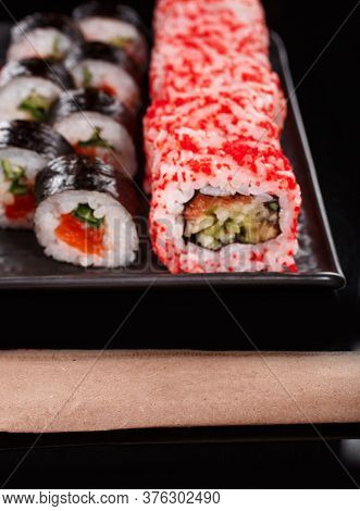 Sushi Set Of Uramaki And Maki With Red Caviar, Salmon And Cucumber. Served On A Black Plate.