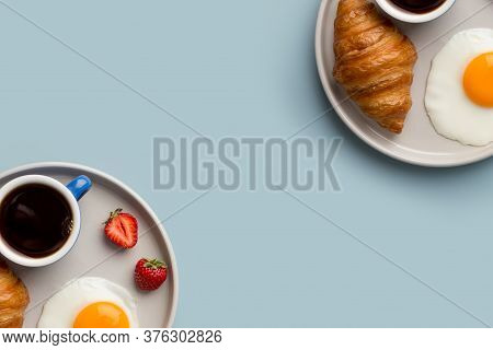 Two Plates With Continental Breakfast On Light Blue Minimal Background. Croissant, Black Espresso Co