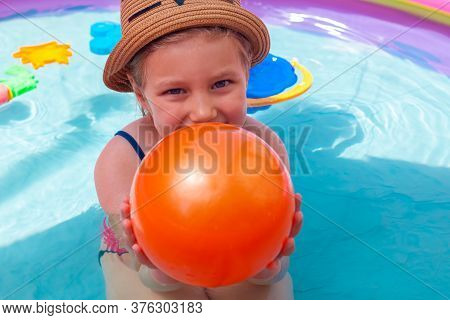 Young Girl Playing In Colorful Rainbow Inflatable Water Swimming Pool With Orange Ball. Happy Child