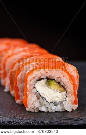Beautiful Sushi Roll Topped With Salmon Stuffed With Cream Cheese On A Black Stone Board.