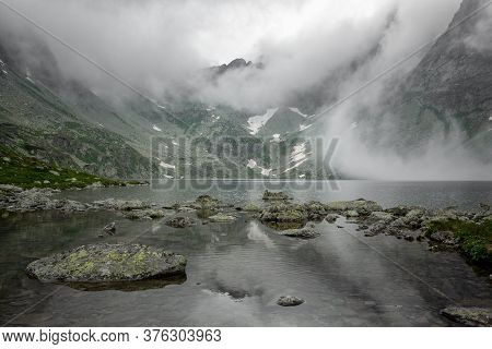 Mountain Lake In The Fog Between Mountains In Slovakia.