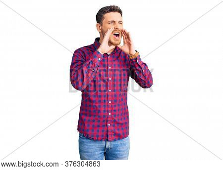 Handsome young man with bear wearing casual shirt shouting angry out loud with hands over mouth