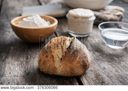 Homemade Sourdough Bread Bun Next To Ingredients - Flour, Water And Starter Yeast