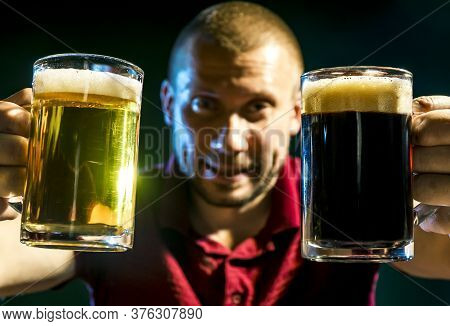 Satisfied Man With Light And Dark Beer In Mugs On A Dark Green Background