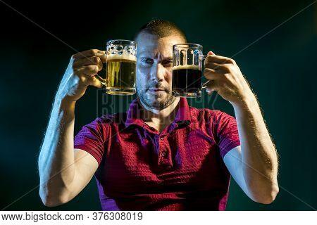 Man Chooses Between Light And Dark Beer In Mugs On A Dark Green Background