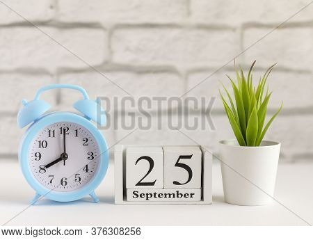 September 25 On A Wooden Calendar Next To The Alarm Clock.september Day, Empty Space For Text.calend