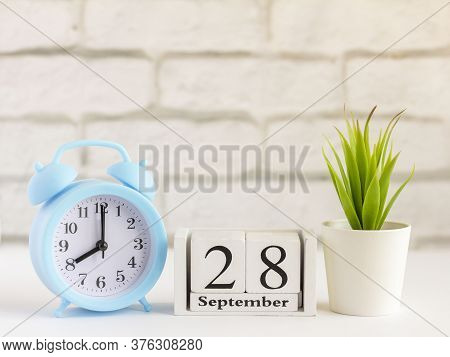 September 28 On A Wooden Calendar Next To The Alarm Clock.september Day, Empty Space For Text.calend