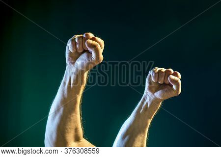 Raised Male Hands With Clenched Hands On A Dark Blue Background