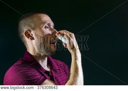 A Man Sprays Medicinal Spray Into The Nose For A Runny Nose On A Dark Background