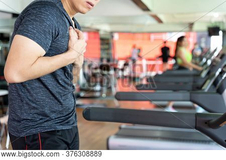 A Man Feeling Exhausted And Suffering From Heart Pain And Injury While Running On Treadmill At Fitne