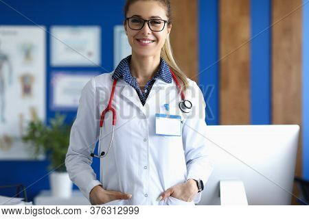 Portrait Of Cheerful Young Woman Posing In Office Wearing Clean White Uniform. Smiling Qualified Fem